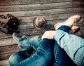 Couple is sitting embracing their legs on wooden floor in sneakers and boots and blue jeans on the outdoors. On the