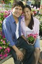 Couple sitting among flowers at plant nursery portrait Stock Image