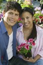 Couple sitting among flowers at plant nursery portrait Stock Photos