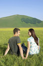 Couple sitting on grassy field at against mountain rear view of young looking each other while together park Stock Photos