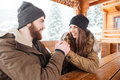 Couple sitting and holding hands in winter happy young on terrace at the wooden table Stock Images