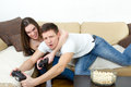 Couple sitting in living room and play video games on console o