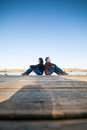 Couple sitting near water on a wooden deck besides a lake Royalty Free Stock Image