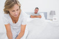 Couple sitting on opposite ends of bed after a fight at home in bedroom Royalty Free Stock Images