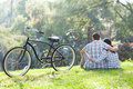 Couple sitting outdoors back view of romantic teenage with bicycle next to them Stock Photos