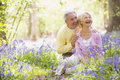 Couple sitting outdoors with flowers smiling Stock Photos