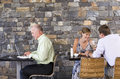 Couple sitting at restaurant table smiling mature businessman working on laptop at next table Royalty Free Stock Photo