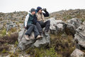 Couple sitting on rock with binoculars while on a hike full length of young and trekking pole Royalty Free Stock Photos