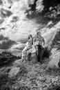 Couple sitting on rock black and white photo of Stock Images