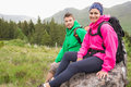 Couple sitting on a rock resting during hike smiling at camera Royalty Free Stock Image