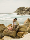 Couple sitting on the rocks at a beach distant view Stock Image