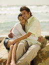 Couple sitting on the rocks at a beach hugging sea in background Stock Photos