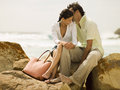 Couple sitting on the rocks at a beach intimate Royalty Free Stock Image