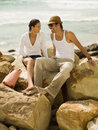 Couple sitting on the rocks at a beach sea in background Royalty Free Stock Images