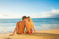 Couple sitting on a sandy tropical beach young together Stock Image