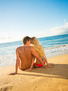 Couple sitting on a sandy tropical beach young together Royalty Free Stock Image