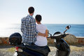 Couple sitting on a scooter near the ocean rear shot of loving and enjoying view Stock Photo