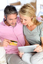 Couple sitting on sofa and buying with credit card in at home doing online shopping Stock Photo