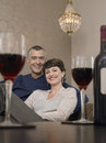 Couple sitting on sofa in front of wineglasses portrait happy table Royalty Free Stock Images