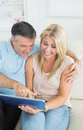 Couple sitting on sofa looking at the tablet and laughing Stock Photography