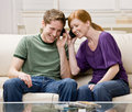 Couple sitting on sofa and sharing headphones Royalty Free Stock Photos