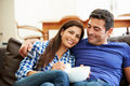 Couple sitting on sofa watching tv together happy with bowl of popcorn Royalty Free Stock Images