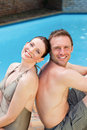 Couple sitting beside the swimming pool Royalty Free Stock Photography