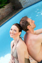 Couple sitting beside the swimming pool Royalty Free Stock Photo