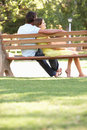Couple Sitting Together On Park Bench Stock Photography