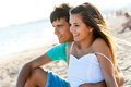 Couple sitting together at sunset cute teen on beach Stock Photo
