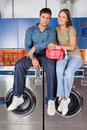 Couple sitting on washing machines portrait of young top of in laundry Royalty Free Stock Image