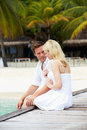 Couple sitting on wooden jetty smiling to each other Royalty Free Stock Photos