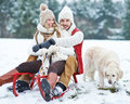 Couple sledding with dog in winter happy toboggan and Royalty Free Stock Photography