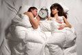 Couple sleeping in bed quiet young together and ignoring alarm clock bell Stock Photos