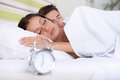 Couple sleeping bed together in with alarm clock Royalty Free Stock Image