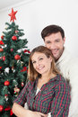 Couple smiling beside the chrismas tree Royalty Free Stock Photo