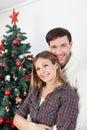 Couple smiling beside the chrismas tree Royalty Free Stock Photo