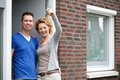 Couple smiling and holding keys to their new house Royalty Free Stock Photo