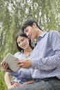 Couple smiling and looking at tablet together Stock Images