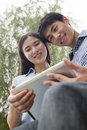 Couple smiling looking at tablet together low angle view Stock Images