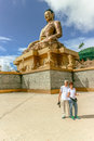 Couple smiling near  giant Buddha Dordenma statue with the blue sky and clouds background, Thimphu, Bhutan Royalty Free Stock Photo