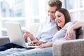 Couple on sofa with laptop young Royalty Free Stock Images