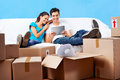Couple on sofa moving in together relaxing couch with laptop tablet computer and boxes Stock Photo