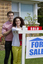 Couple sold home vertical posing with sign after selling Stock Photography