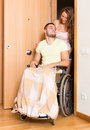 Couple with spouse in wheelchair near door