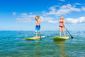 Couple stand up paddle surfing in hawaii beautiful tropical ocean active beach lifestyle Royalty Free Stock Images