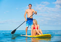 Couple stand up paddle surfing in hawaii beautiful tropical ocean active beach lifestyle Stock Images