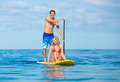 Couple stand up paddle surfing in hawaii beautiful tropical ocean active beach lifestyle Stock Photo