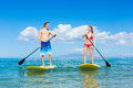 Couple stand up paddling in hawaii attractive Royalty Free Stock Photos