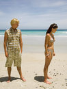 Couple standing away from each other on beach Royalty Free Stock Photography